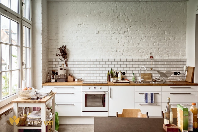 Inviting European-style kitchen illuminated by a wall of windows. Room is comfortably cluttered with papers stacked on a side table and several bottles and packages on the table. Fashionably distressed brick walls, painted white, give the room a rough, rustic feel.